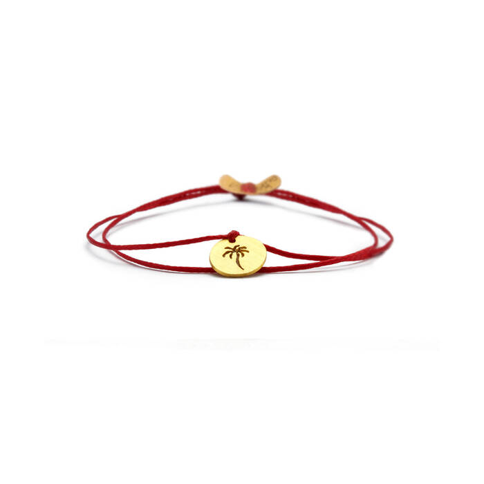 Bracelet in 18k gold on red cord.